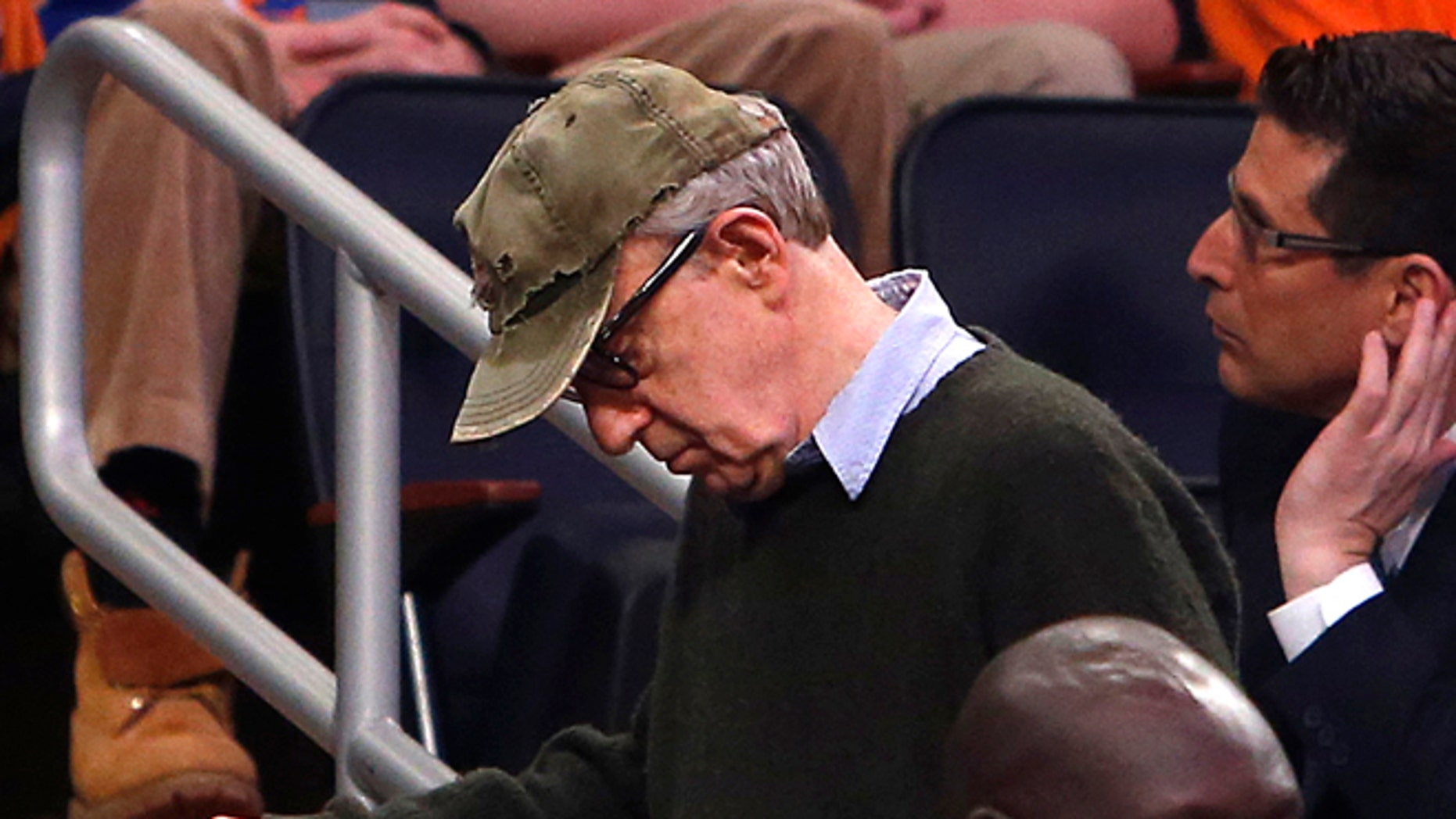 Feb. 1, 2014: Filmmaker Woody Allen, left, leaves late in the fourth quarter of an NBA basketball game between the Miami Heat and the New York Knicks.