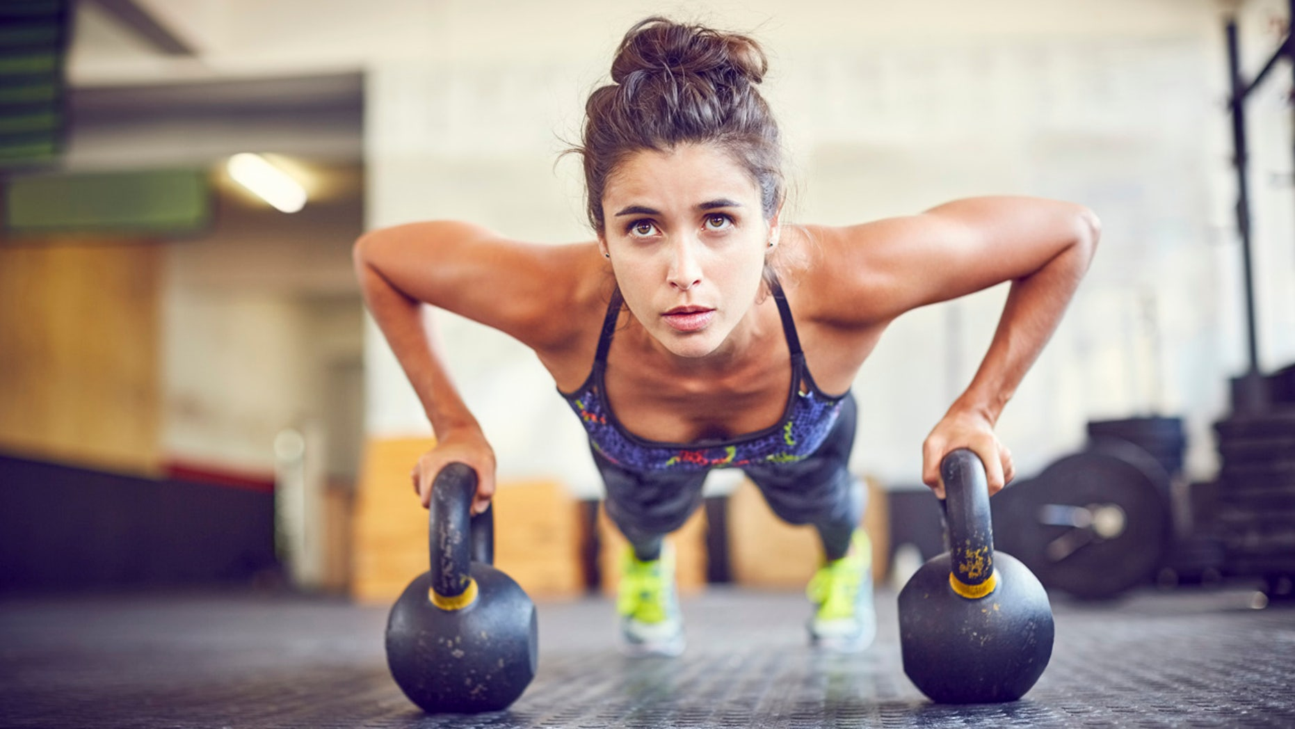 Focused athlete doing push-ups on kettlebells. Female is exercising in gym. Sporty woman is in health club.