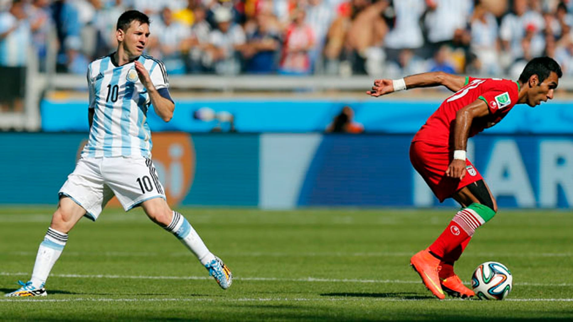 June 21, 2014: Argentina's Lionel Messi, left, watches as Iran's Mehrdad Pooladi takes the ball away from him during the group F World Cup soccer match between Argentina and Iran at the Mineirao Stadium in Belo Horizonte, Brazil.