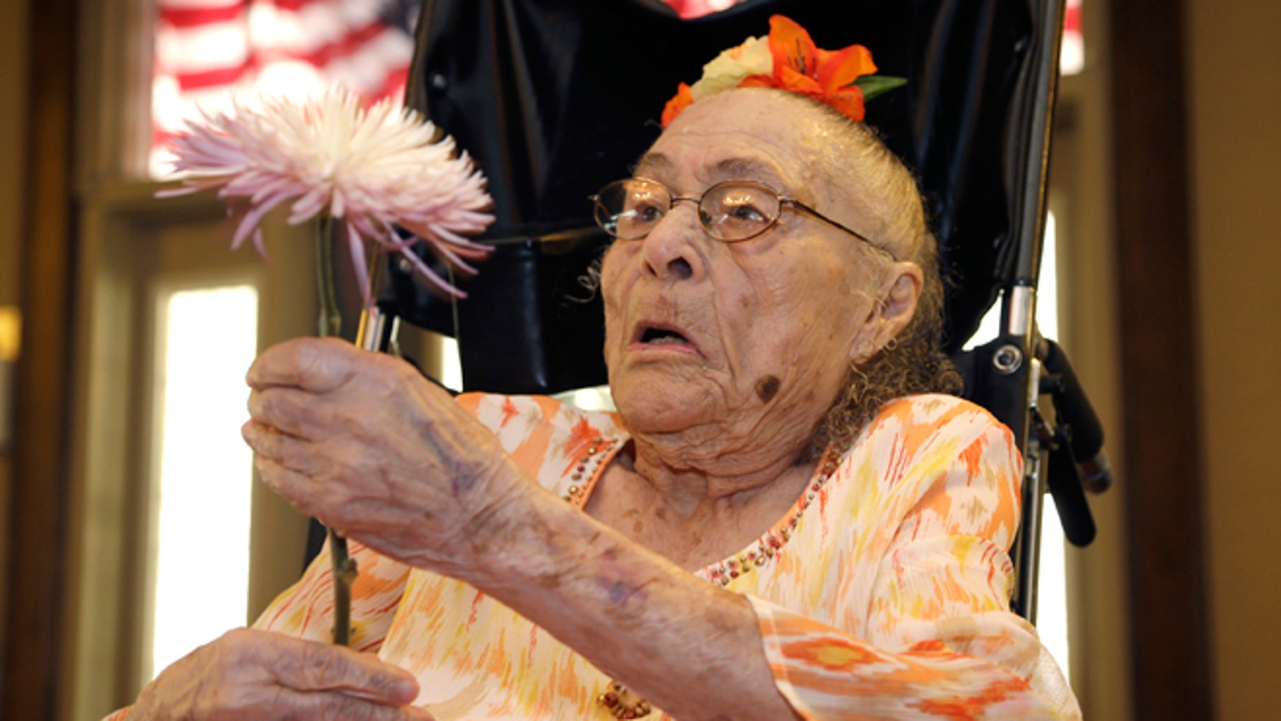 July 3, 2014: Gertrude Weaver holds a flower given to her a day before her 116th birthday at Silver Oaks Health and Rehabilitation Center in Camden, Ark.