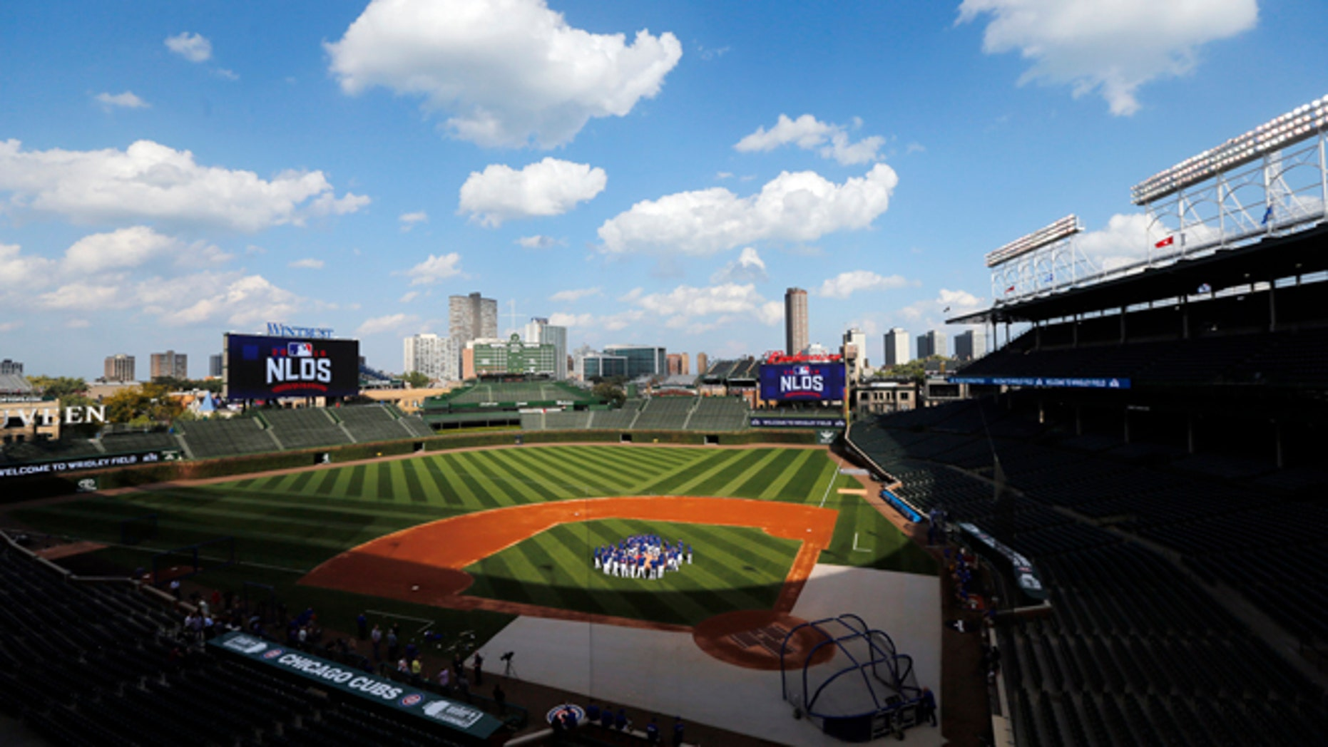 FILE - In this Oct. 5, 2016 file photo, Chicago Cubs players gather around manager manager Joe Maddon on the mound at Wrigley Field as they prepare for Game 1 of the National League Division Series baseball game, in Chicago.