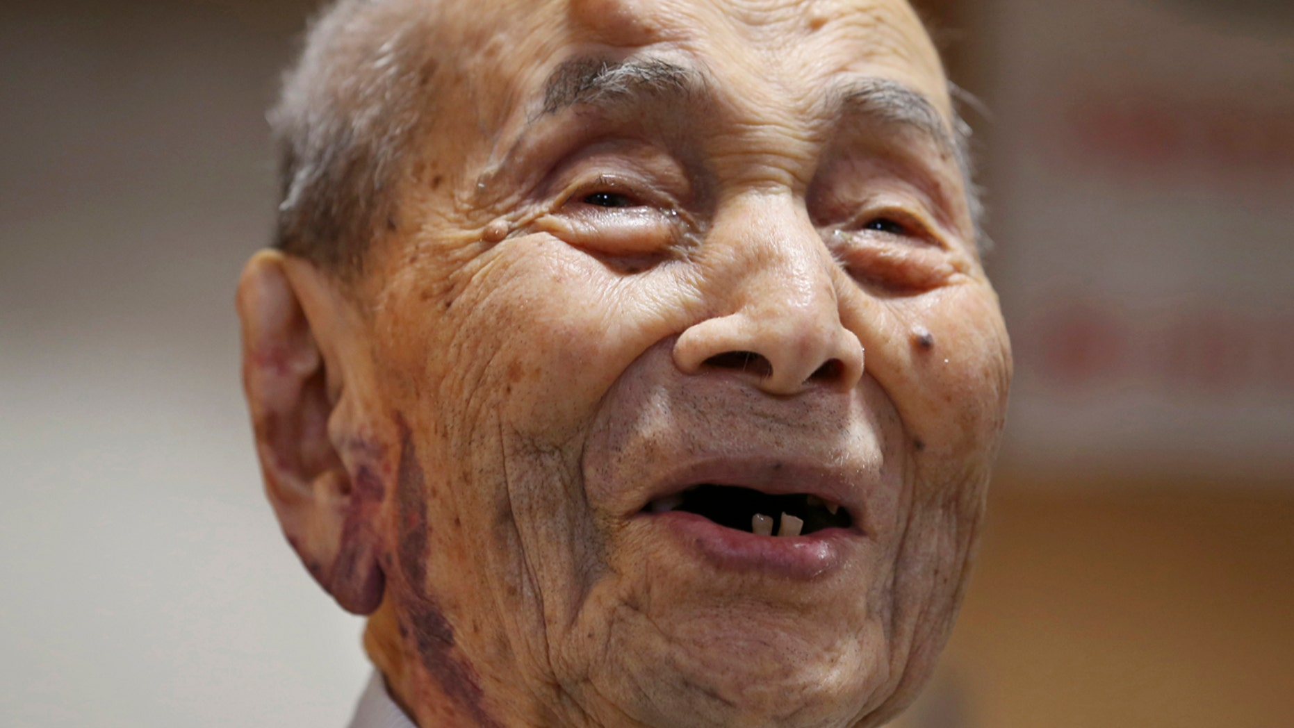 FILE - In this Aug. 21, 2015 file photo, Yasutaro Koide smiles upon being formally recognized as the world's oldest man by the Guinness World Records at a nursing home in Nagoya, central Japan. (AP Photo/Koji Sasahara, File)