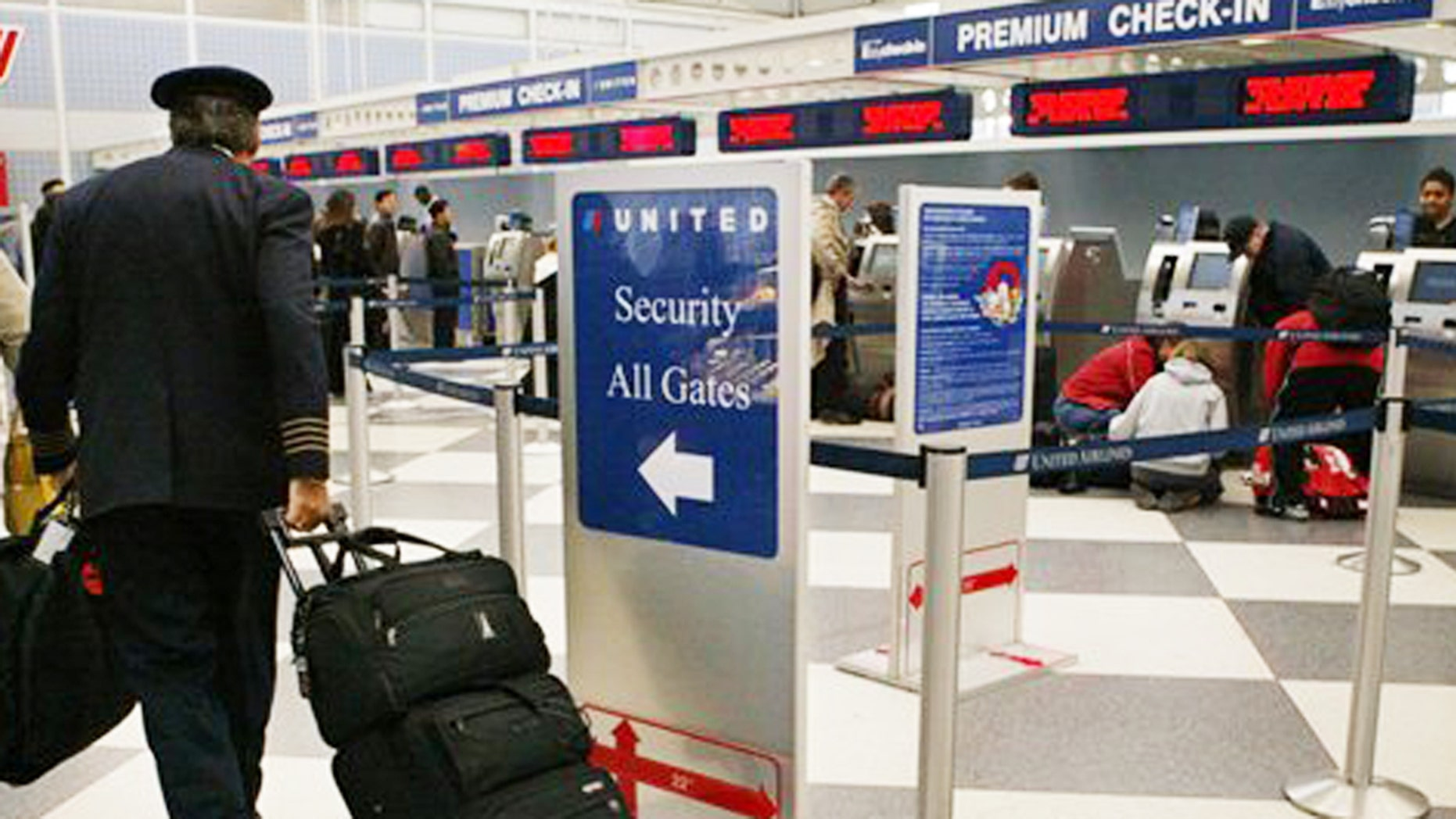A United Airlines pilot walks to security check point at Chicago's O'Hare International Airport, one of the nation's busiest airports.