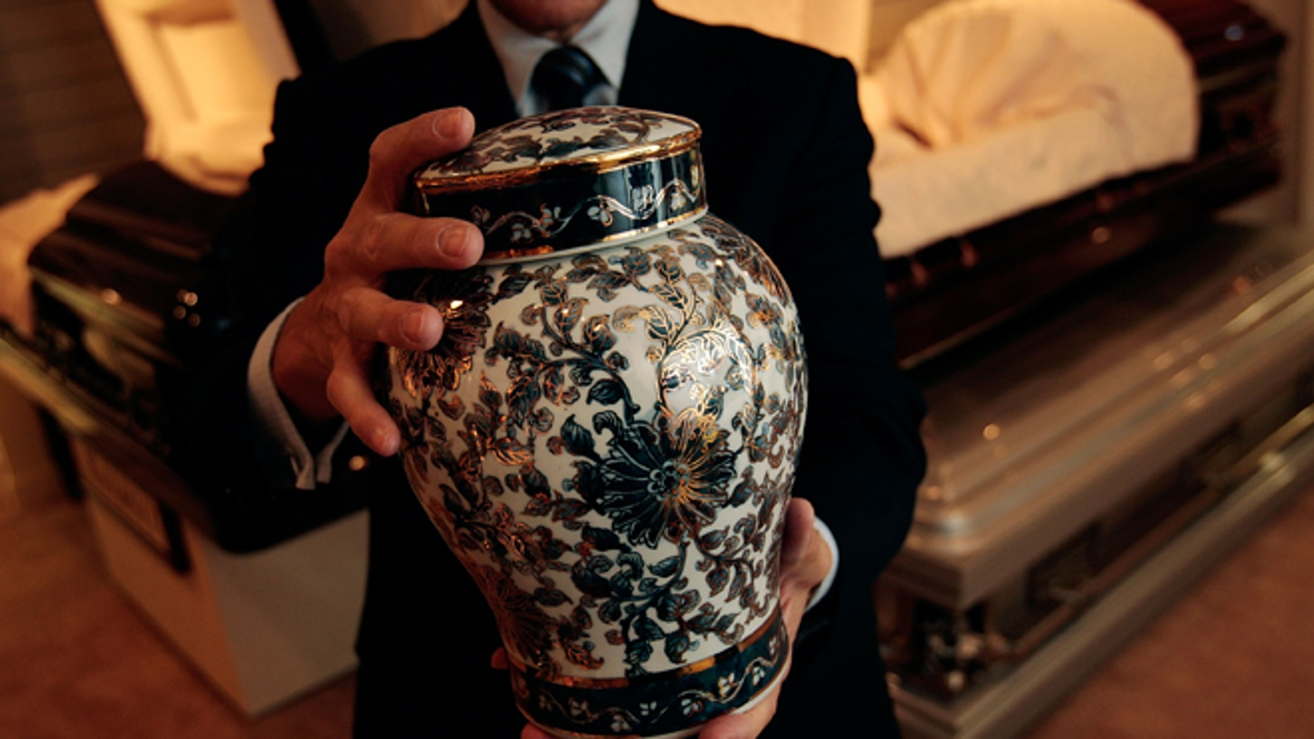 NEW YORK - NOVEMBER 20:  Funeral director Peter DeLuca, owner of Greenwich Village Funeral Home, holds a cremation urn in the showroom of his funeral parlor on November 20, 2008 in New York City. New technologies, such as flat screen televisions for video memorials, ornate and even sports-team themed cremation urns are also slowly being introduced at funeral homes. Despite the currently languishing economy, the funeral home world is readying for an upswing nationally, as the recession-resistant business prepares for an expected rise in death rates as baby boomers start to reach old age in the coming decade.  (Photo by Chris Hondros/Getty Images)