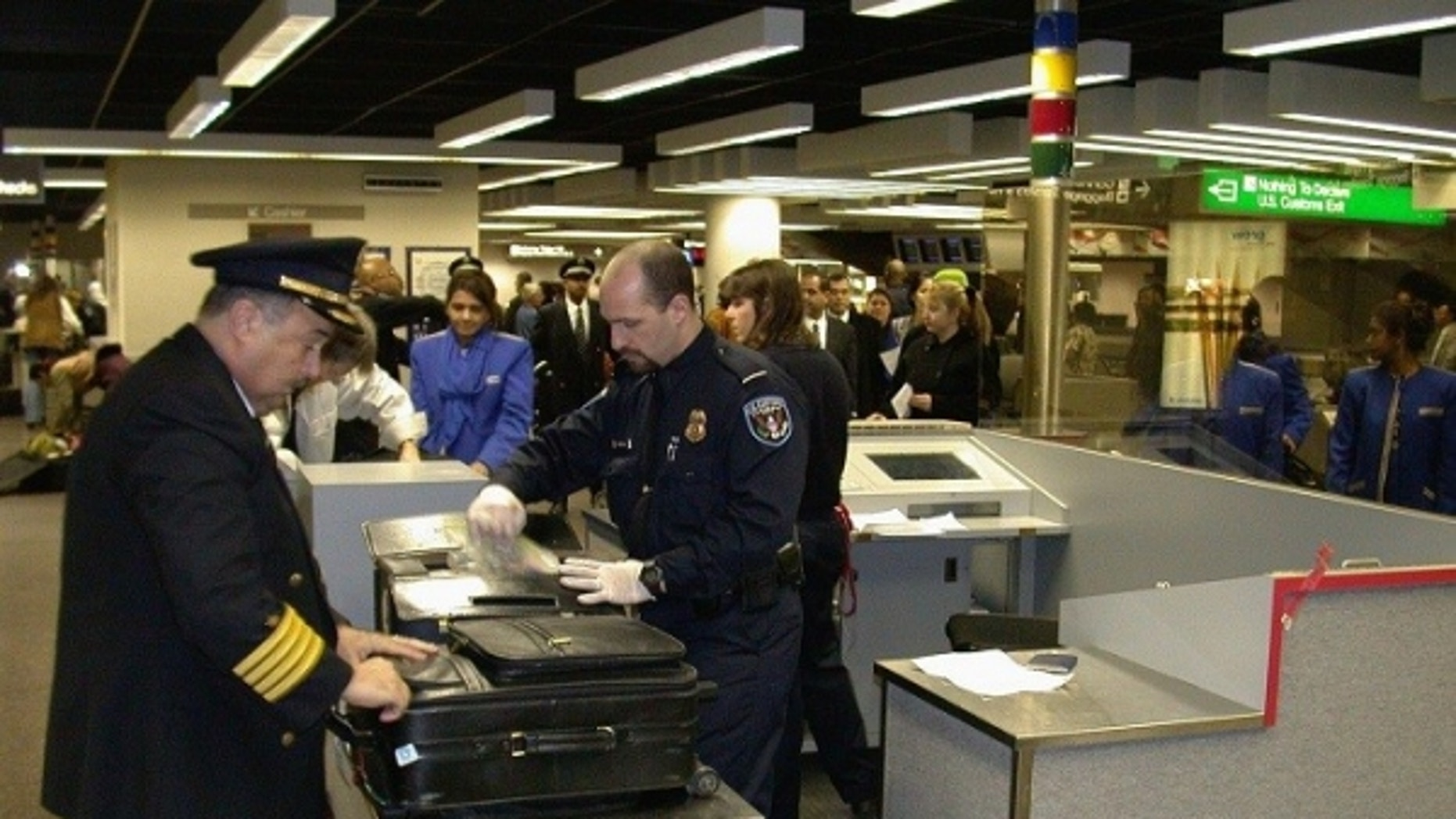 Customs agents inspect airline passenger bags at New York's John F. Kennedy Airport.