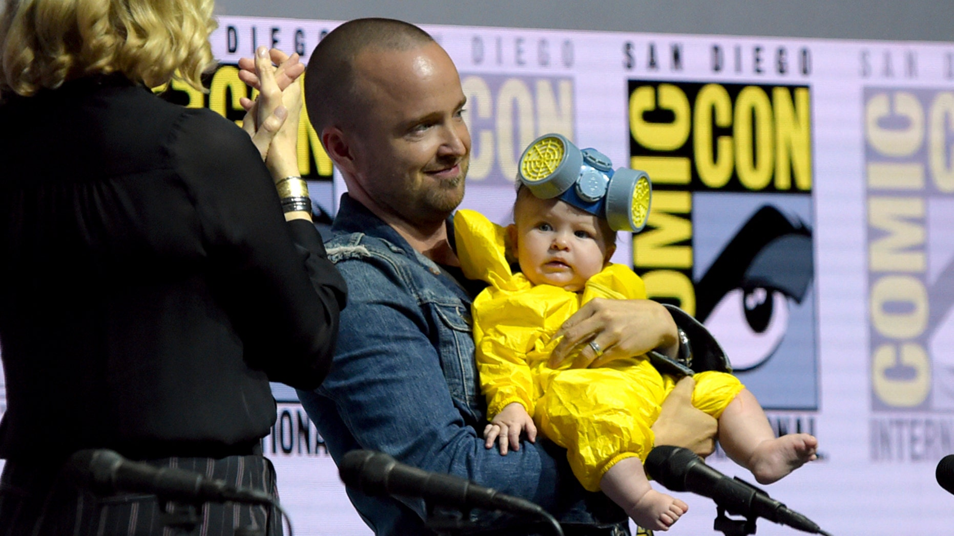 """Anna Gunn, from left, looks on as Aaron Paul holds his daughter Story Annabelle, dressed as his character Jesse Pinkman, at the """"Breaking Bad"""" 10th Anniversary panel on day one of Comic-Con International on Thursday, July 19, 2018, in San Diego.(Photo by Richard Shotwell/Invision/AP)"""