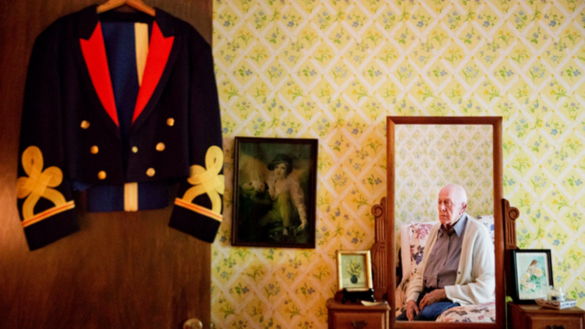Frank Gleason, 96, a retired colonel with the Office of Strategic Services, looks at his old blue mess dress uniform hanging on a door as he sits in his home in Atlanta, Wednesday, Sept. 28, 2016.