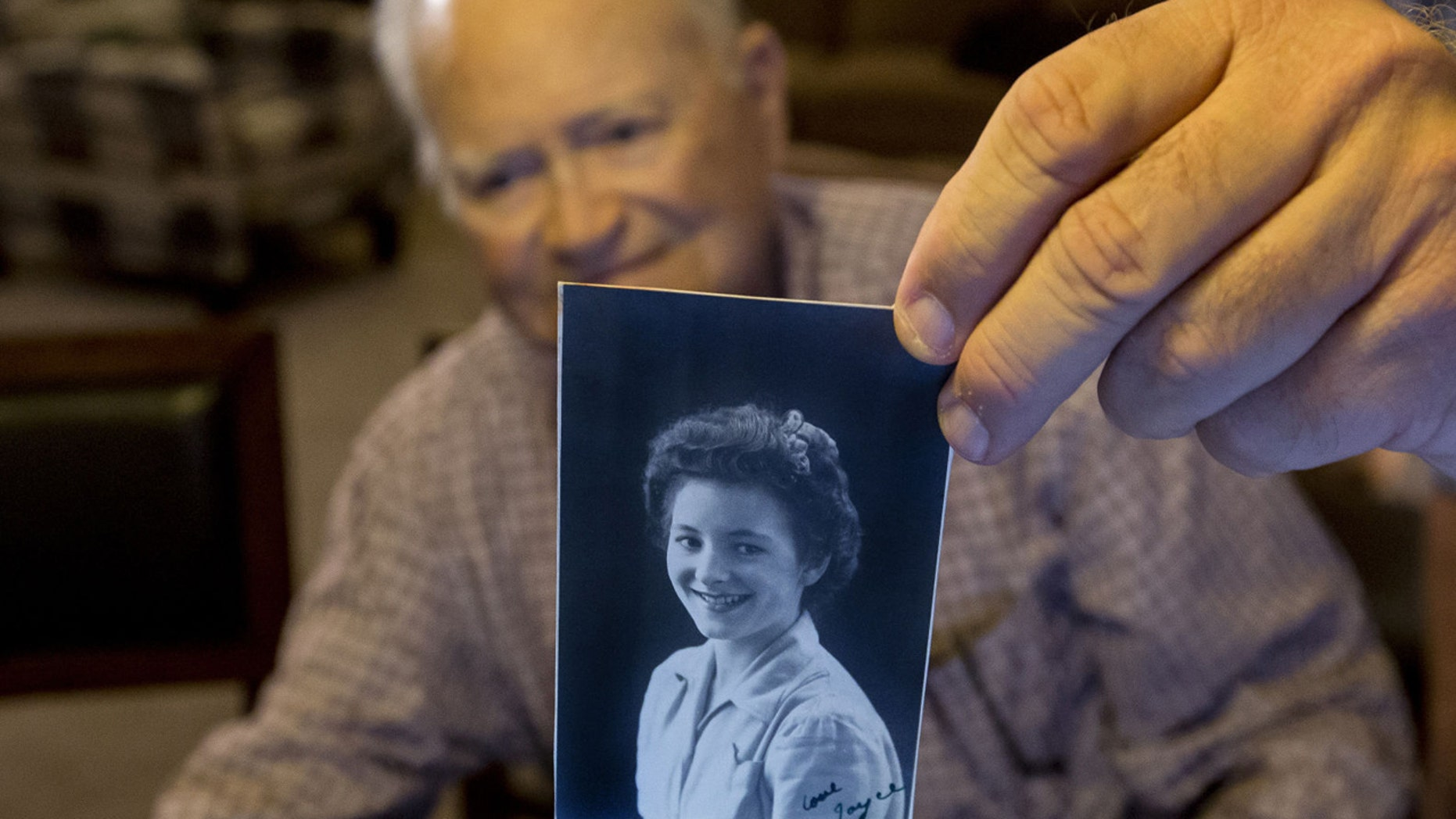 FILE - In this Nov. 6, 2015 file photo, Norwood Thomas, holds up a photo of with Joyce Morris at his home in Virginia Beach, Va. Thomas arrived in Australia Wednesday to reunite with Morris, his girlfriend during World War II. (Bill Tiernan/The Virginian-Pilot via AP)
