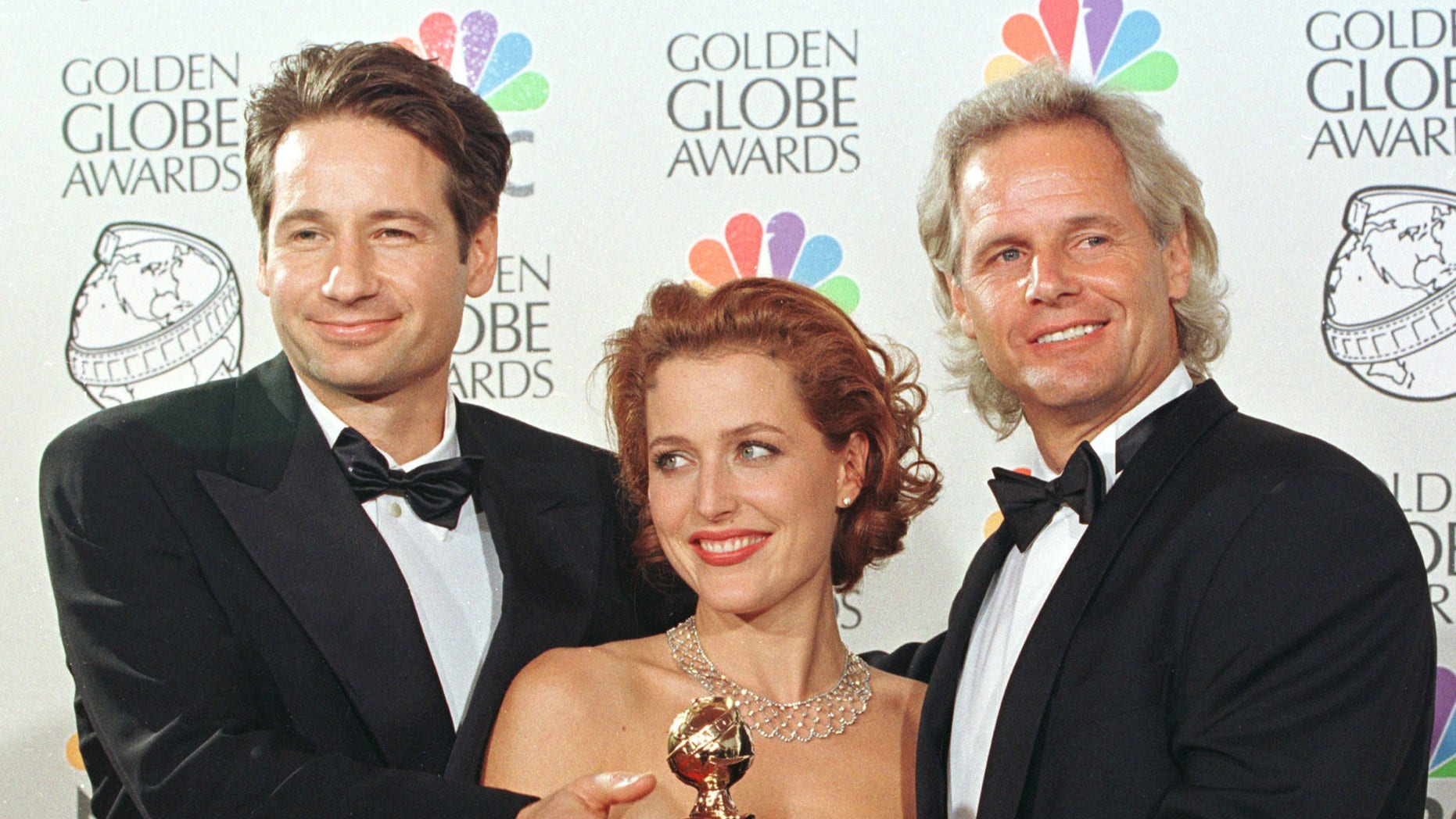 Stars David Duchovny (L) and Gillian Anderson (C) pose with X-Files creator Chris Carter, after the show was named Best Television Drama at the 55th annual Golden Globe Awards in Beverly Hills, January 18. The Golden Globe Awards, sponsored by the Hollywood Foreign Press Association, honor excellence in film and television. - RTXIMBF