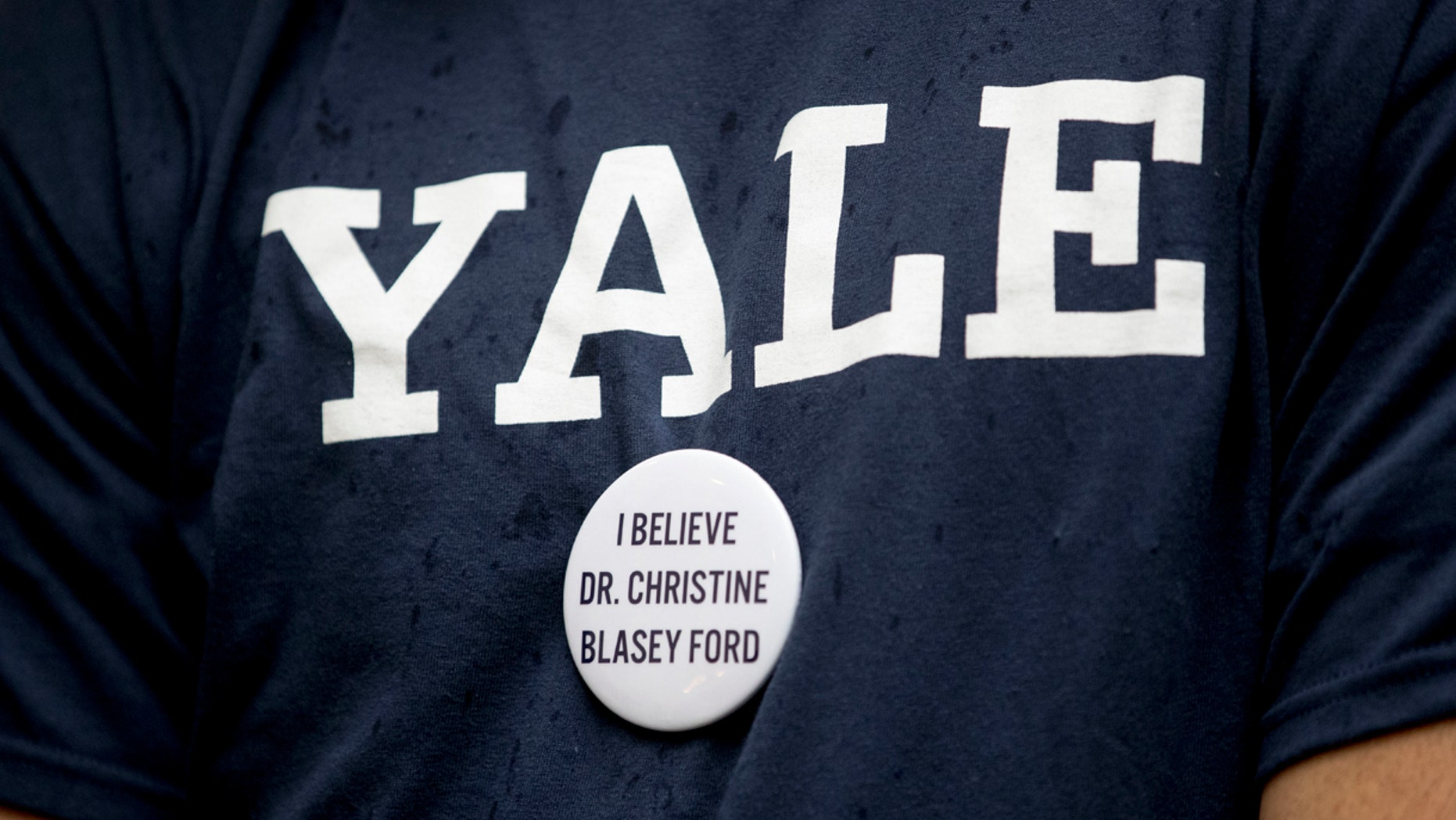 """A protester against Judge Brett Kavanaugh wears a Yale shirt with a button that reads """"I Believe Dr. Christine Blasey Ford, on Capitol Hill in Washington on Sept. 24."""