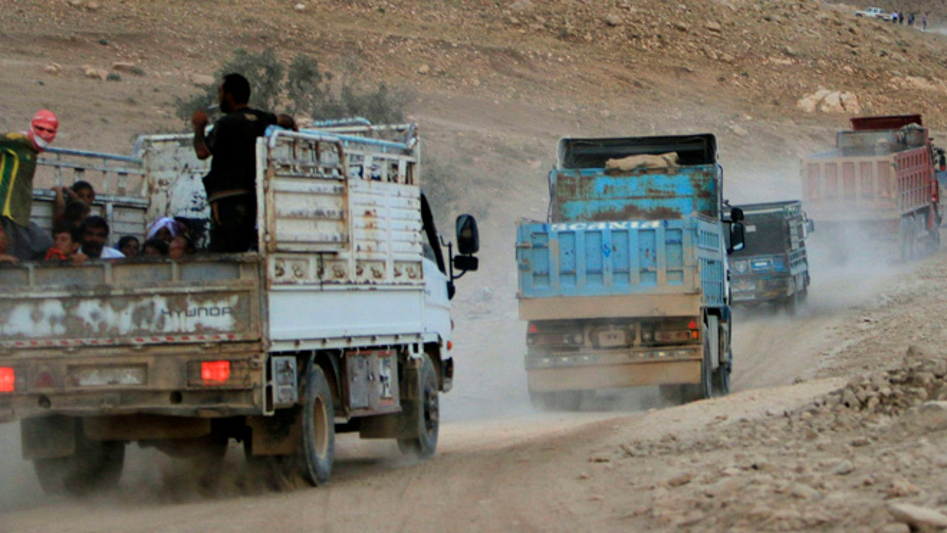 August 13, 2014: Displaced people from the Yazidi religious minority, fleeing violence from forces loyal to the Islamic State in Sinjar town, ride trucks as they are evacuated from Mount Sinjar in northern Iraq with the help of members of the Kurdish People's Protection Units (YPG), as they make their way towards Newrooz camp in Syria's al-Hasakah province.