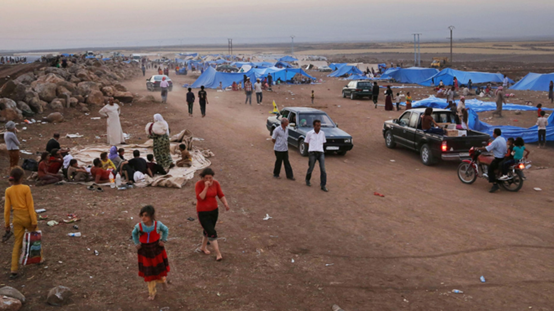 Aug. 10, 2014: Displaced Iraqis from the Yazidi community settle at a camp at Derike, Syria.