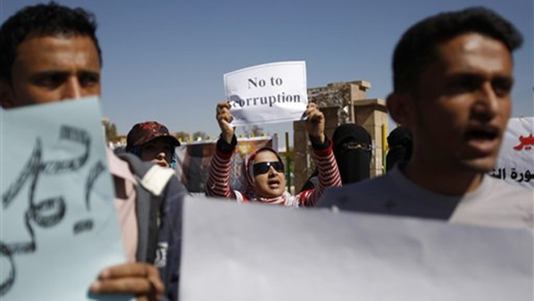 Yemeni demonstrators hold placards during an anti-government protest in Sanaa, Yemen, Feb. 10.