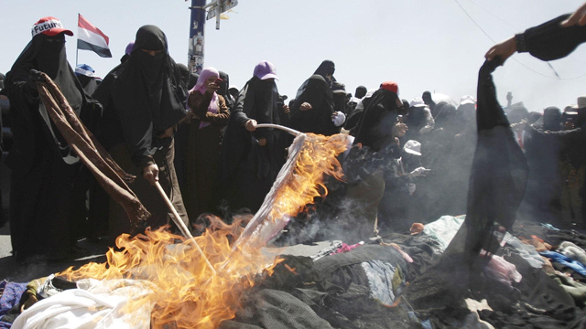 Oct. 26, 2011: Protesting Yemeni women burn their veils during a demonstration demanding the resignation of Yemeni President Ali Abdullah Saleh in Sanaa, Yemen.