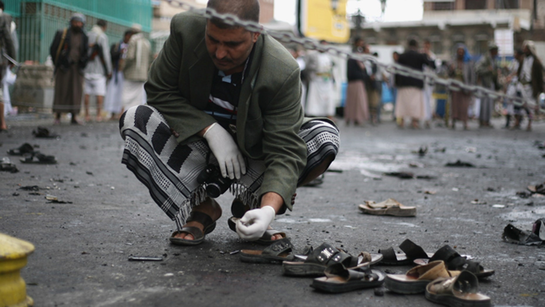 Oct. 9: A Yemeni security official inspects the site of a suicide bombing in Sanaa, Yemen.