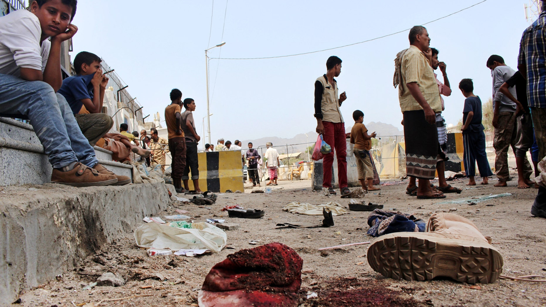 May 23, 2016: People gather at the scene after a pair of suicide bombings attack in the southern city of Aden, Yemen.