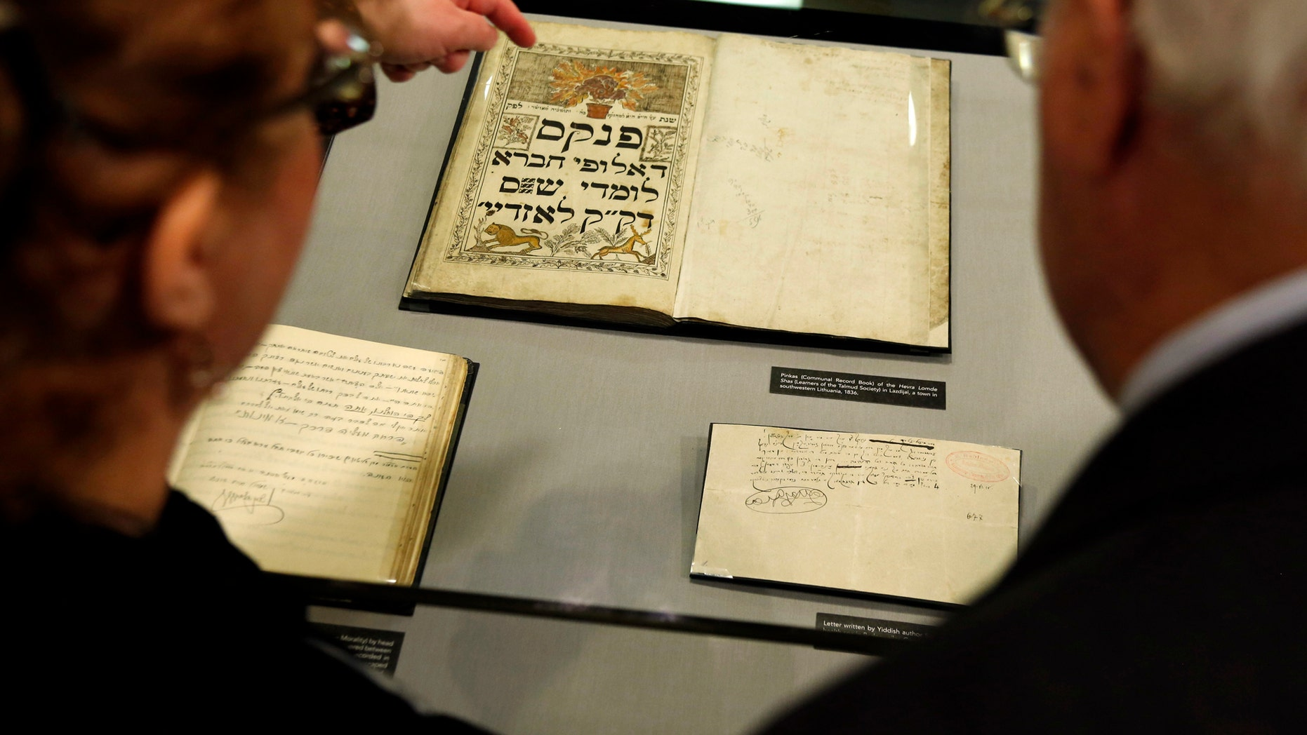People look over record book from 1836 that is displayed at the YIVO Institute for Jewish Research in New York, Tuesday, Oct. 24, 2017. These documents along with more than 170,000 other pages are part of a recently discovered trove of Jewish materials from Lithuania thought to have been destroyed during the Holocaust. (AP Photo/Seth Wenig)