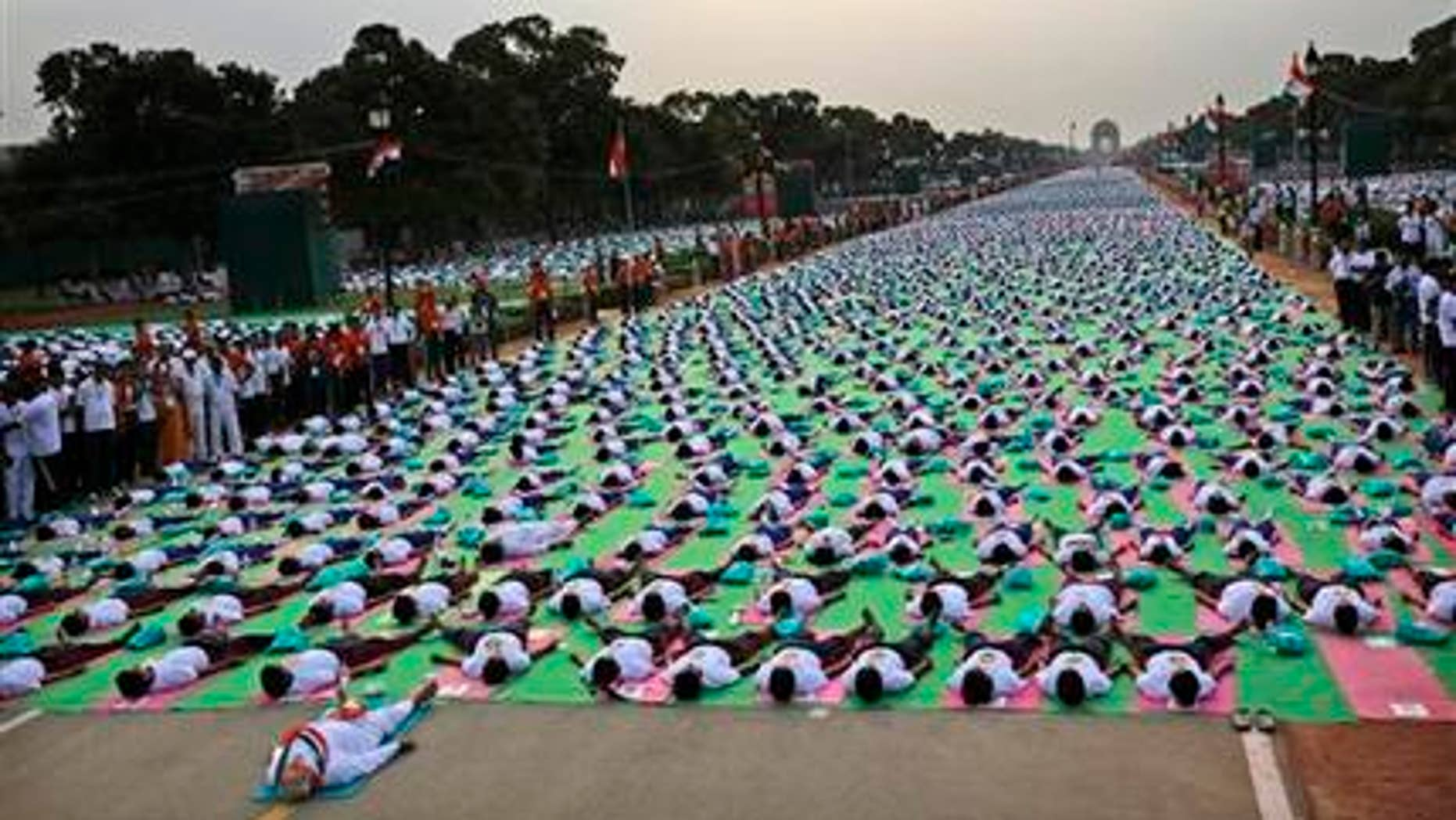 June 21, 2015: Indian Prime Minister Narendra Modi, left front, lies down on a mat as he performs yoga along with thousands of Indians on Rajpath, in New Delhi, India.