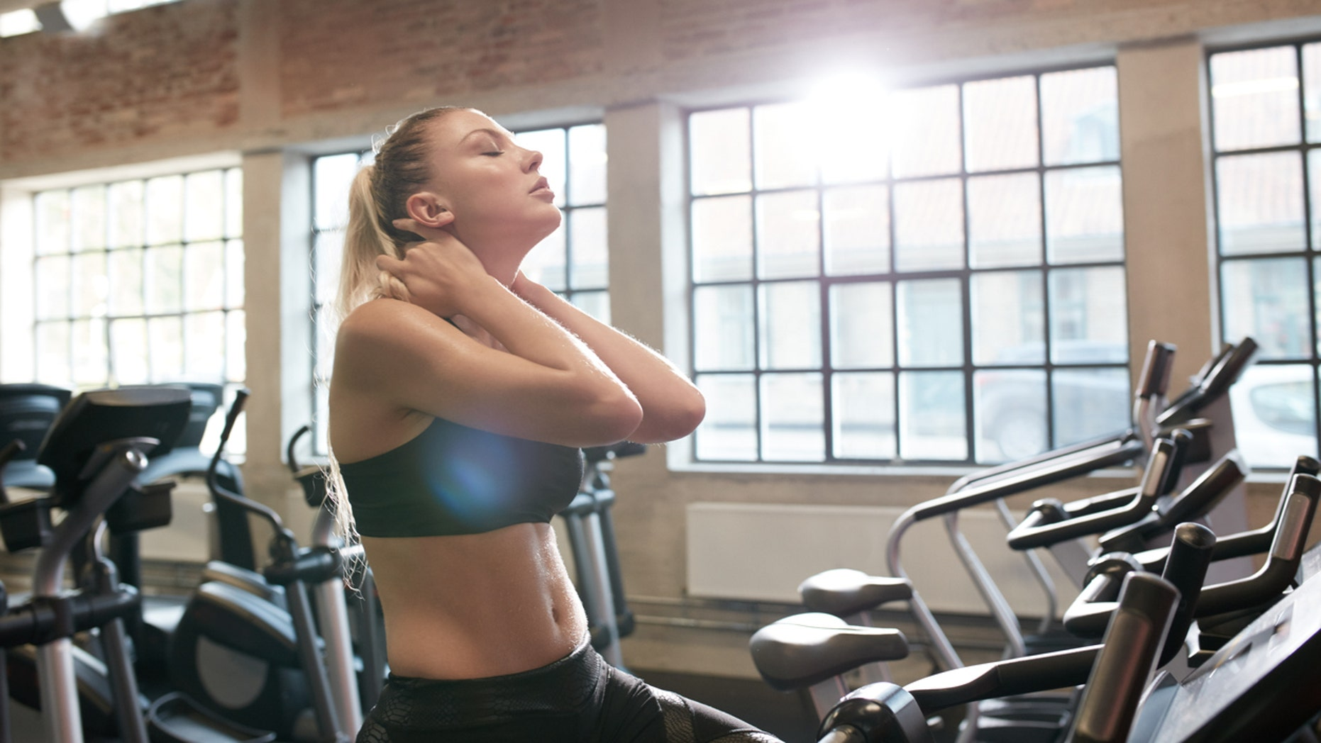 Young woman tired after intense workout on gym bike. Relaxing her neck muscles after workout in fitness club.