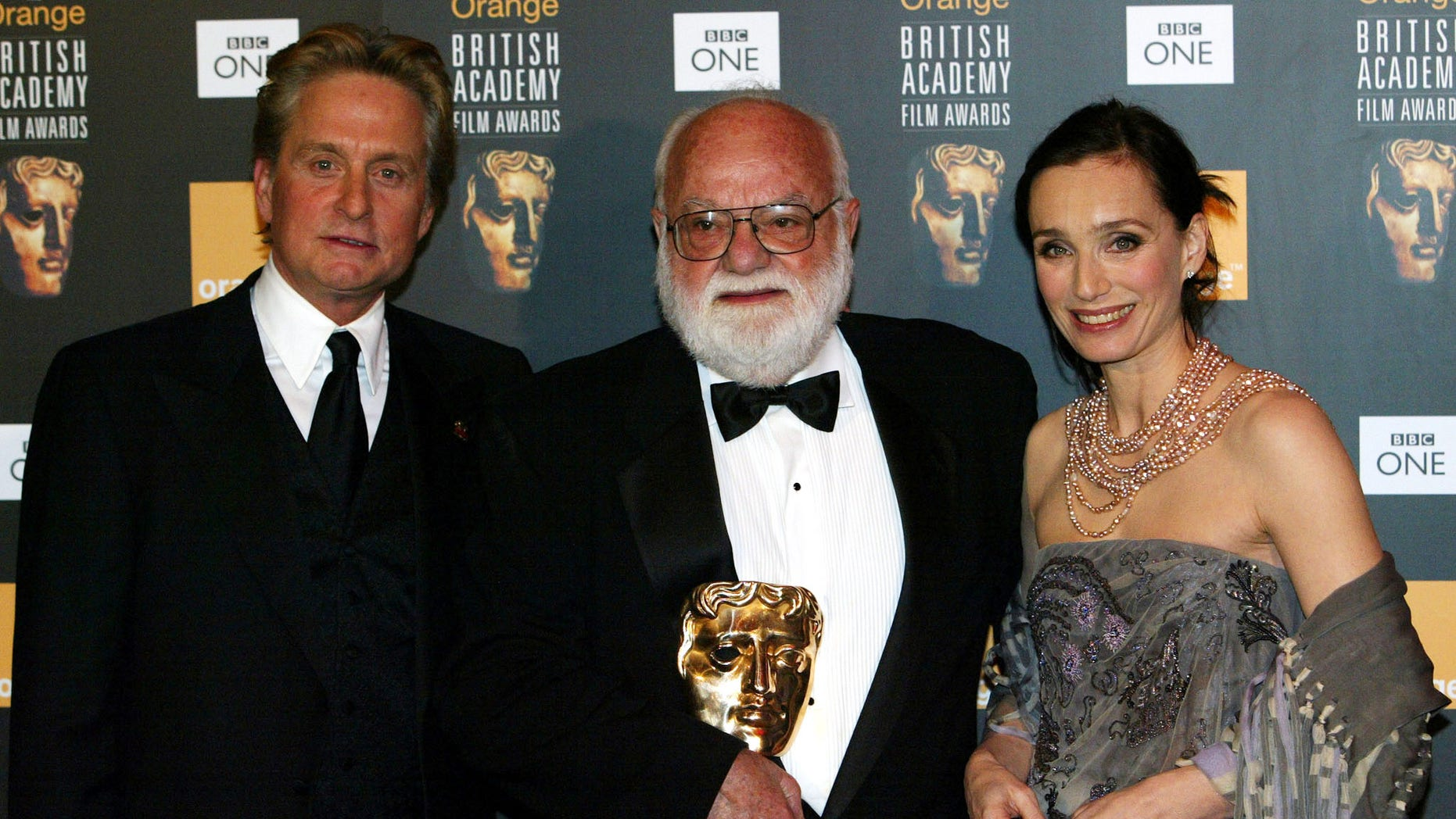 February 23, 2003. Michael Douglas presents producer Saul Zaentz with The Academy Fellowship as he stands flanked by British actress Kristen Scott-Thomas during the British Academy of Film and Television Arts (BAFTA) Awards at the Odeon Leicester Square in London.