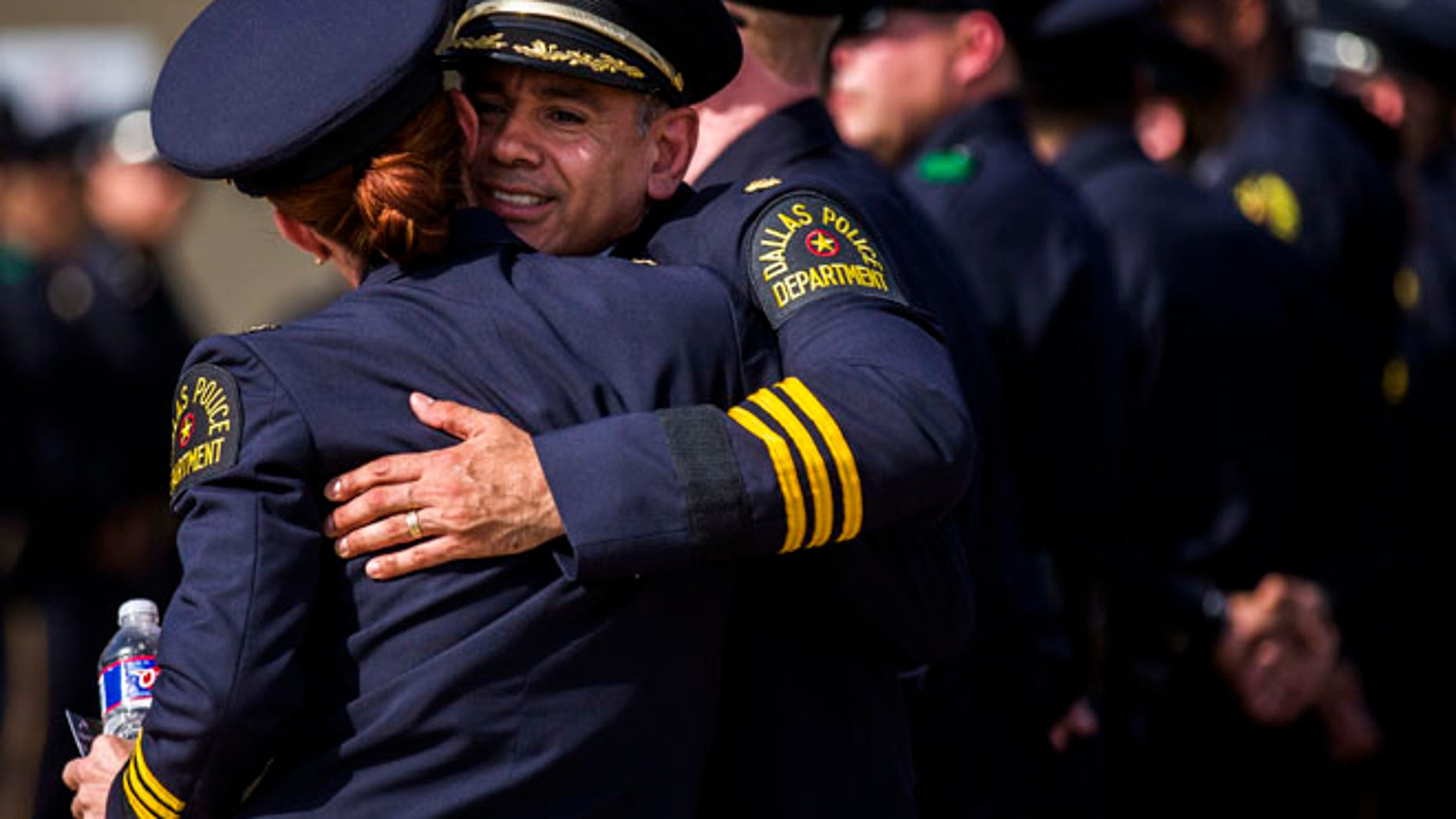 Police officers greet each other before a funeral service for Dallas police officer Patrick Zamarripa on Saturday, July 16, 2016, in Fort Worth, Texas.