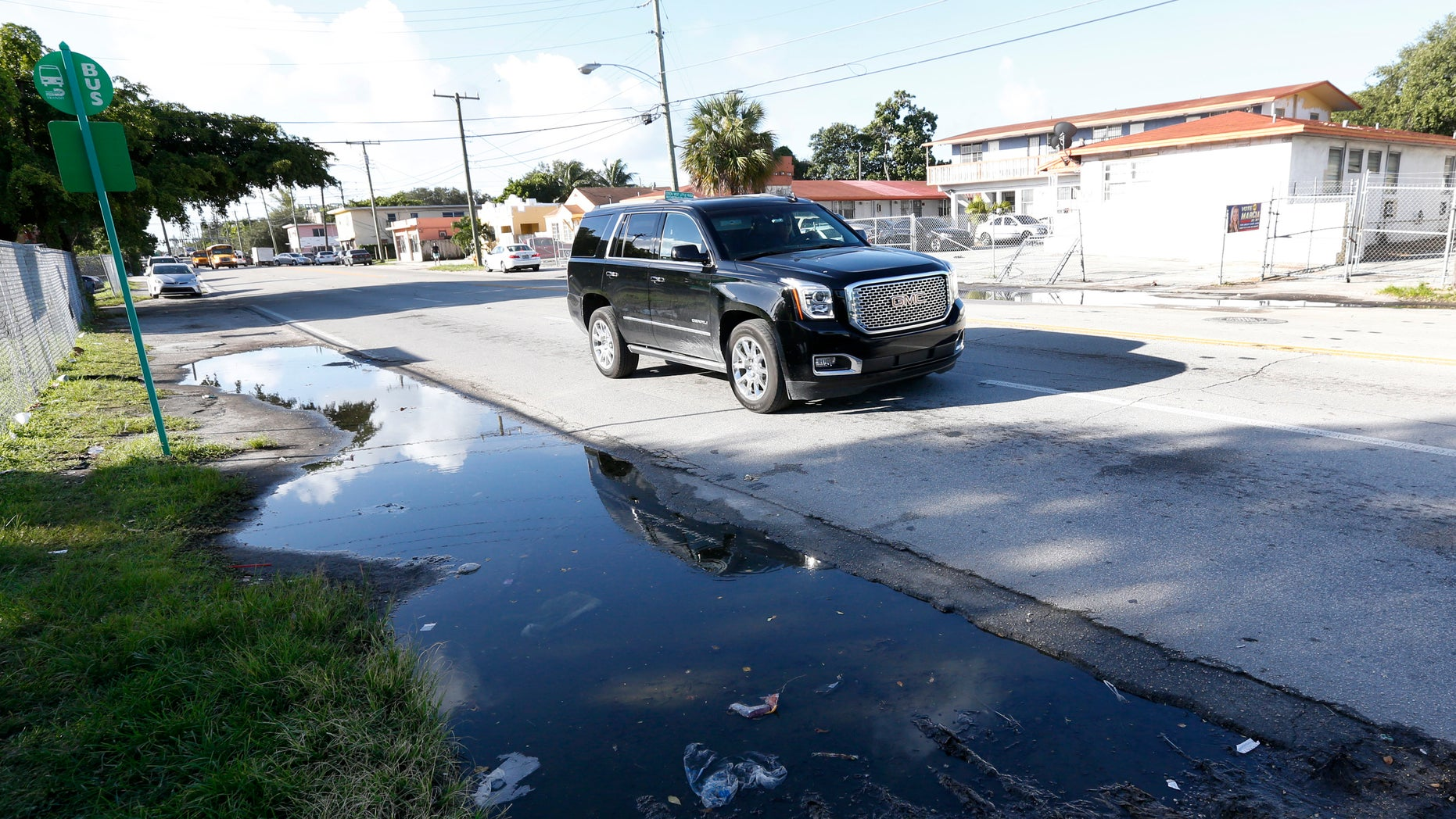 A vehicle drives past a pool of standing water where mosquitoes can breed, Friday, Oct. 14, 2016, in Miami. Thursday, Fla., Governor Rick Scott announced that the Florida Department of Health has confirmed that local transmission of the Zika virus is occurring in a new, approximately square mile area, in Miami-Dade County. (AP Photo/Wilfredo Lee)