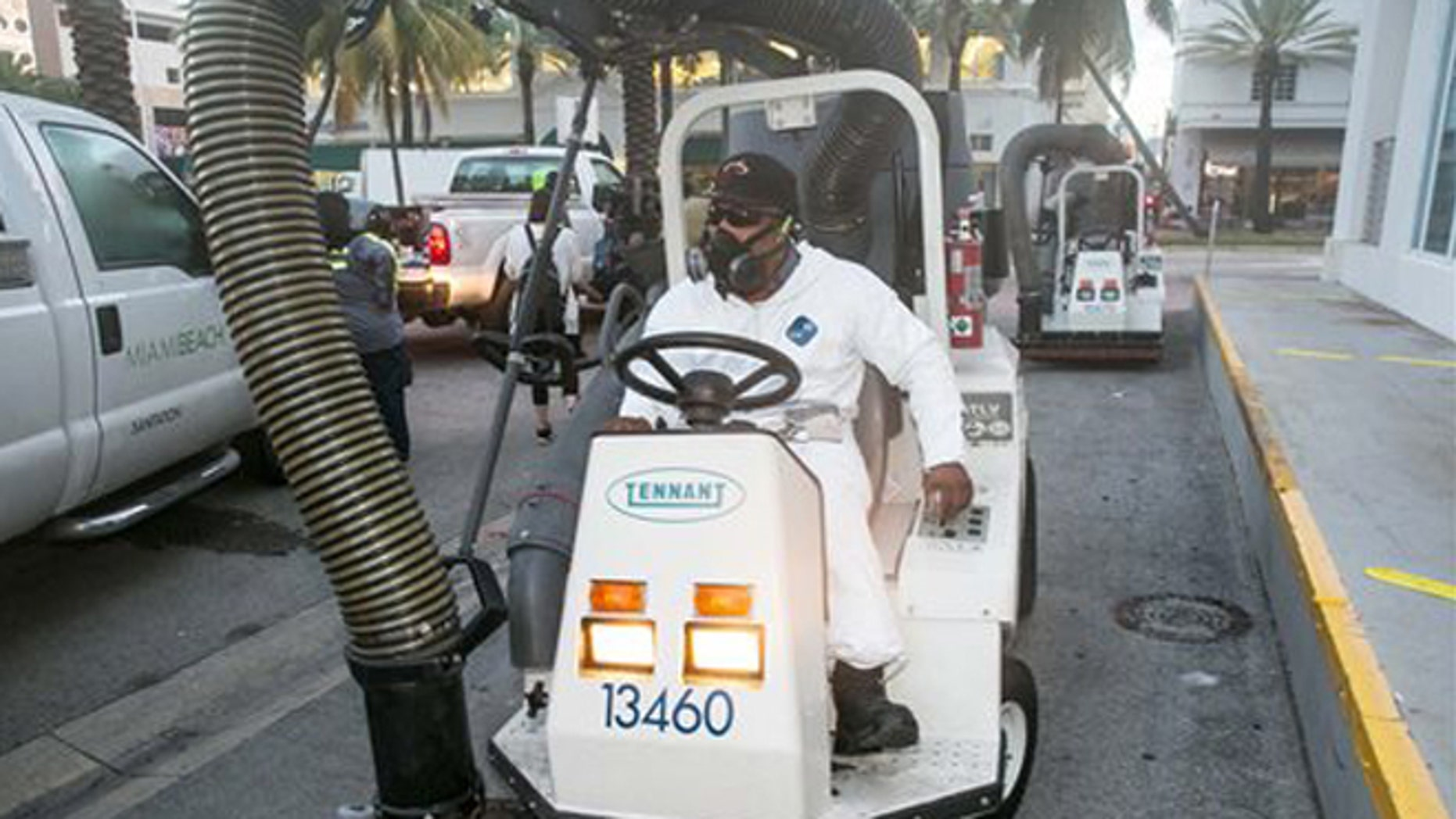 A City of Miami Beach Sanitation worker gets ready to clean the alleyways of South Beach, sucking up still waters and debris with a mobile vacuum, Friday, Aug. 19, 2016, Miami Beach, Fla., as part of the city's Zika clean-up. (C.M. Guerrero/El Nuevo Herald via AP)