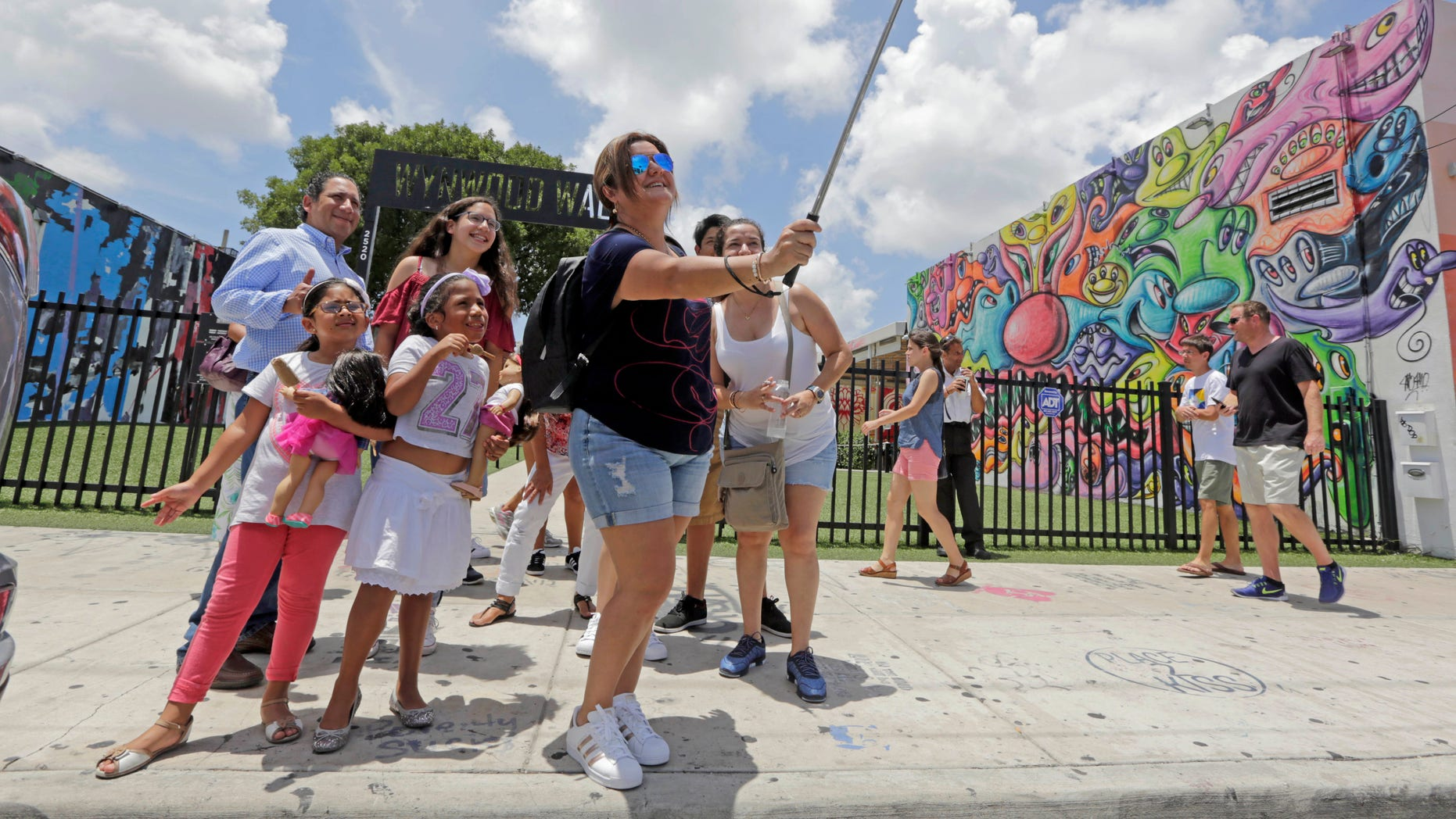 In this Friday, Aug. 5, 2016, file photo, a family from Peru takes a selfie in front of the Wynwood Walls, in the Wynwood area of Miami.