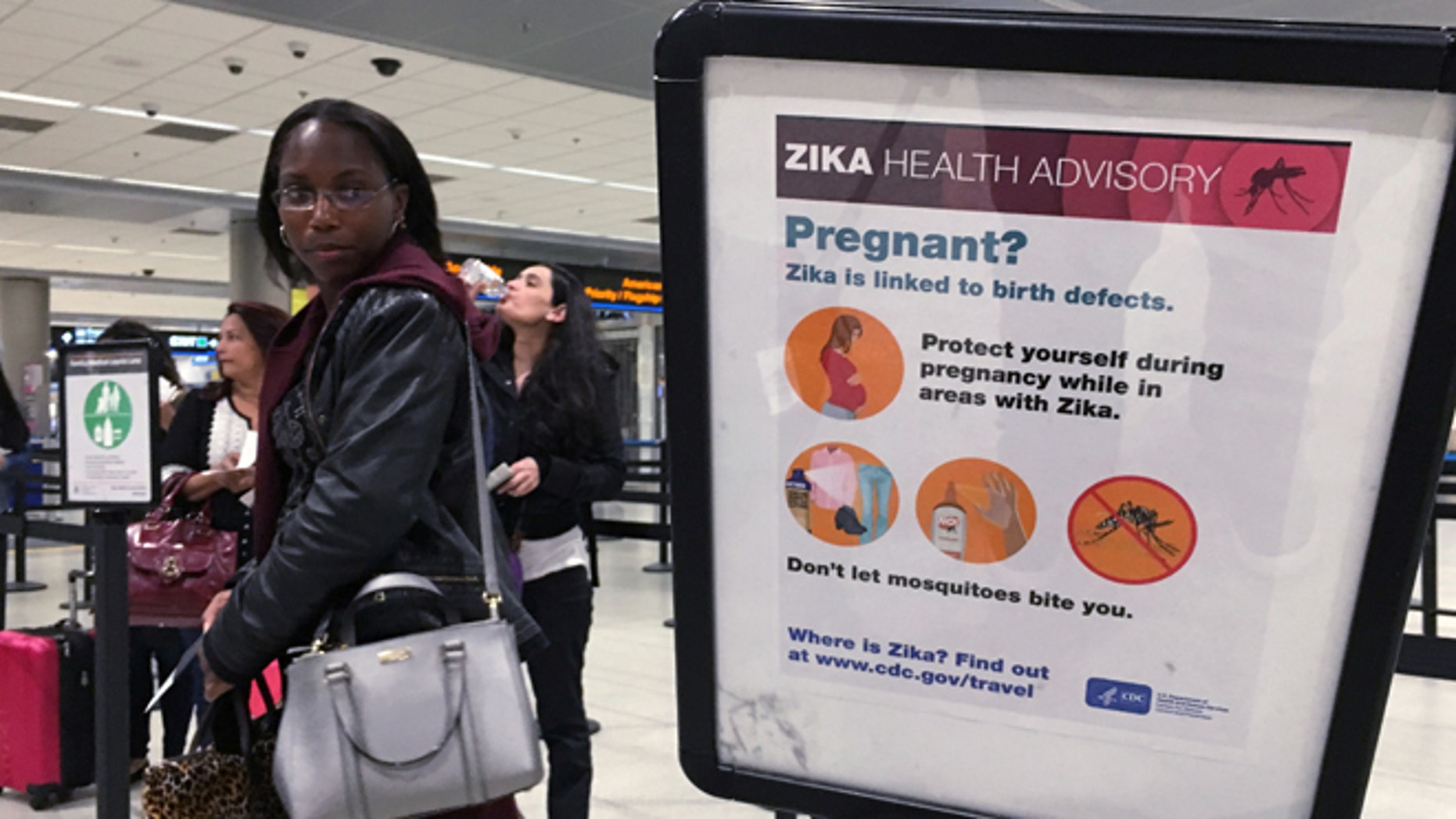 May 23, 2016: A woman looks at a Center for Disease Control (CDC) health advisory sign about the dangers of the Zika virus as she lines up for a security screening at Miami International Airport in Miami, Florida, U.S.