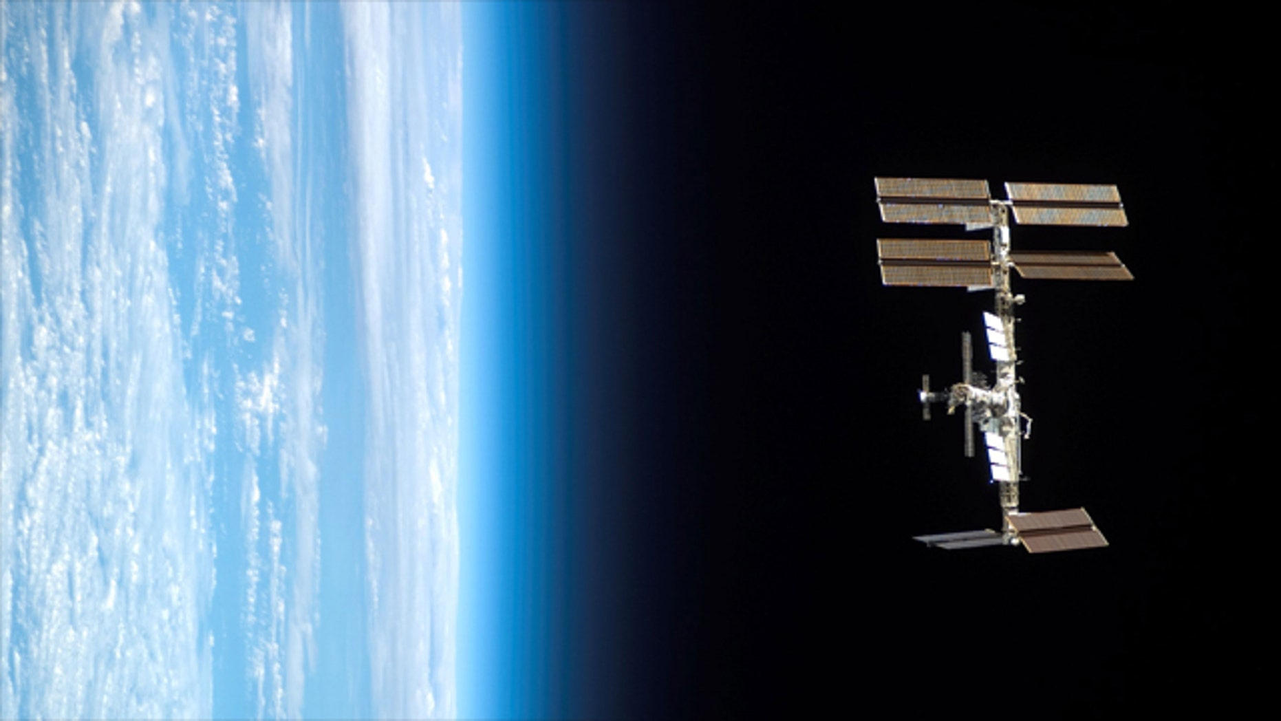 Backdropped by Earth's horizon and the blackness of space, the International Space Station is seen from Space Shuttle Endeavour as the two spacecraft begin their relative separation.