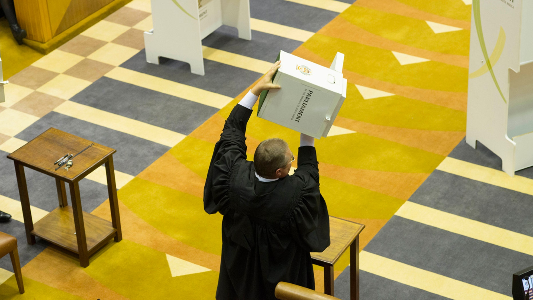 A parliamentary officer shows an empty ballot box to the South African parliament before voting for or against the motion of no confidence against South African president, Jacob Zuma in the South African parliament in Cape Town, South Africa, Tuesday, Aug. 8, 2017.