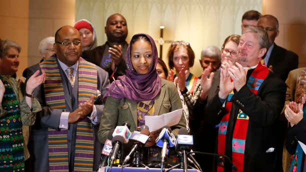 Dec. 16, 2015: Wheaton College associate professor Larycia Hawkins, center, is greeted with applause from supporters as she begins her remarks during a news conference in Chicago