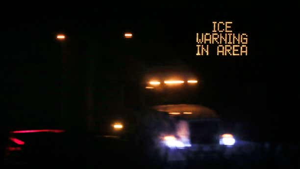 Jan. 14, 2017: Traffic moves past an icing warning sign at night on I-70 west Lawrence, Kan.
