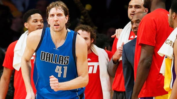 Dallas Mavericks' Dirk Nowitzki, left, runs on the court while Los Angeles Lakers' Kobe Bryant, right, reacts to Nowitzki making a shot over Lakers' Julius Randle, not seen, to give the Mavericks the lead in the closing seconds of an NBA basketball game Tuesday, Jan. 26, 2016, in Los Angeles. The Mavericks won 92-90. (AP Photo/Danny Moloshok)