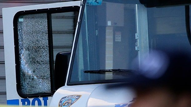 An NYPD vehicle with a cracked window sits on the scene where a police officer was fatally shot in the Bronx section of New York, July 5, 2017.
