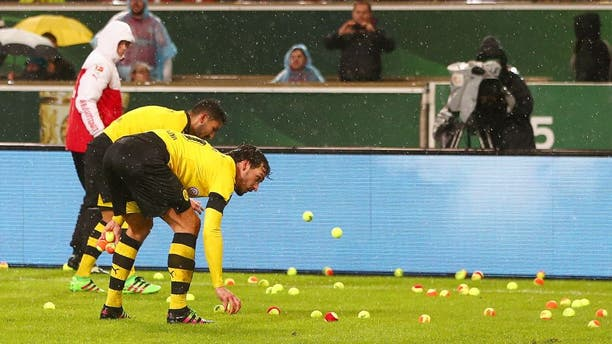 STUTTGART, GERMANY - FEBRUARY 09: Players remove tennis balls thrown by Dortmund fans from the pitch during the DFB Cup Quarter Final match between VfB Stuttgart and Borussia Dortmund at Mercedes-Benz Arena on February 9, 2016 in Stuttgart, Germany. (Photo by Alex Grimm/Bongarts/Getty Images)