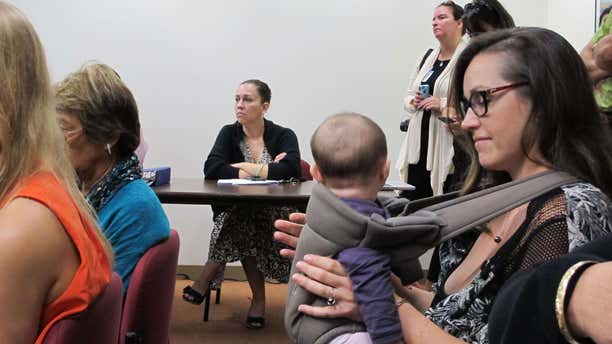 Colleen Chapman, an Oahu resident who's concerned about her children's exposure to pesticide, listens to testimony while holding her daughter at a legislative hearing on Tuesday, Feb. 9, 2016 in Honolulu.