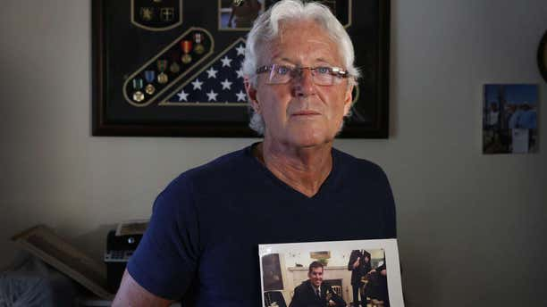 """In this February 2017 photo, William Owens holds a photo of his youngest son Navy SEAL William """"Ryan"""" Owens in Lauderdale by the Sea, Fla."""
