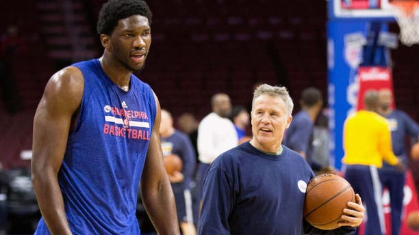 Feb 20, 2015; Philadelphia, PA, USA; Philadelphia 76ers head coach Brett Brown (left) walks with center Joel Embiid (21) after running him threw drills prior to a game against the Indiana Pacers at Wells Fargo Center. Mandatory Credit: Bill Streicher-USA TODAY Sports