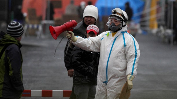 March 15: Officials wearing clothing to protect against radiation directs people to a center to scan residents who have been within 20 kilometers of the Fukushima Dai-ichi nuclear plant damaged by Friday's earthquake in Koriyama, Fukushima Prefecture, Japan.