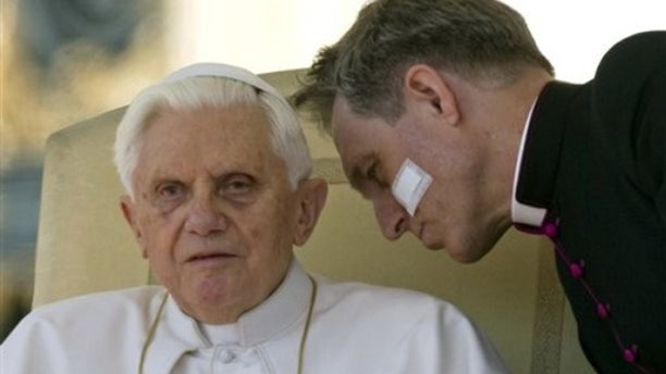 Pope Benedict XVI listens to his personal secretary Georg Gaenswein during a general audience in St. Peter's square at the Vatican, Wednesday, March 17, 2010. (AP)