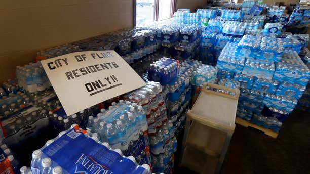 FILE - In this Friday, Feb. 5, 2016 file photo, hundreds of cases of bottled water are stored at Our Lady of Guadalupe Church in Flint, Mich.