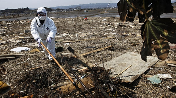 April 13: A police officer in protective suit searches for missing people in Minami Soma, Fukushima Prefecture, northeastern Japan.