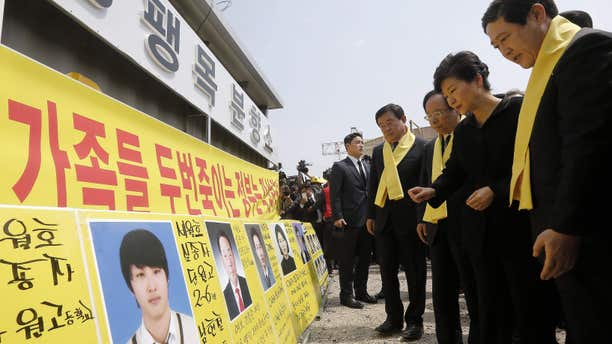 April 16, 2015: South Korean President Park Geun-hye, second from right, looks at portraits of the victims of the sunken ferry Sewol as she arrives to offer her condolences to the bereaved relatives of the victims at a port in Jindo, South Korea,