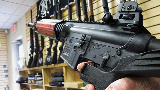 """In this Feb. 1, 2013, file photo, an employee of North Raleigh Guns demonstrates how a """"bump"""" stock works at the Raleigh, N.C., shop. Lawmakers could now consider banning the devices in the wake of the Las Vegas shooting."""