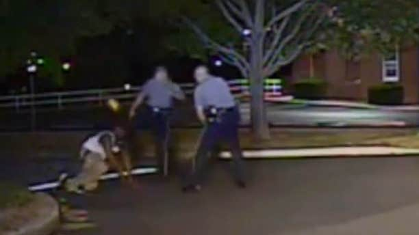 Aug. 24, 2013: In this photo made from a police dash camera video and released by the Dover Police Department, Dover Police Cpl. Thomas Webster, center, kicks Lateef Dickerson in the face as Dickerson is following orders to get on the ground during an arrest in Dover, Del.