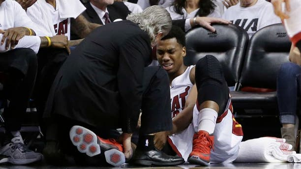 Miami Heat center Hassan Whiteside (21) is attended by a team member after he was injured during the first half of Game 3 of an NBA second-round playoff basketball series against the Toronto Raptors, Saturday, May 7, 2016, in Miami. (AP Photo/Alan Diaz)