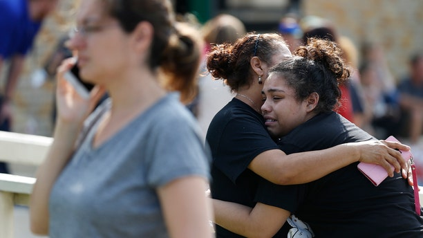 Students console each other following a school shooting at Santa Fe High School.