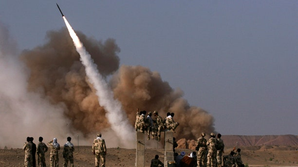 June 28: In this photo released by the semi-official Iranian Mehr News Agency, Iranian Revolutionary Guards personnel, foreground, watch the launch of a Zelzal missile during military maneuvers outside the city of Qom, Iran.