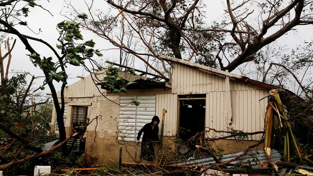A man looks for valuables in the damaged house of a relative after the area was hit by Hurricane Maria in Guayama, Puerto Rico September 20, 2017.